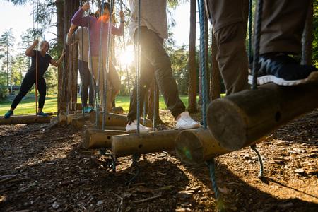 Business People Crossing Swinging Logs In Forest Foto de archivo