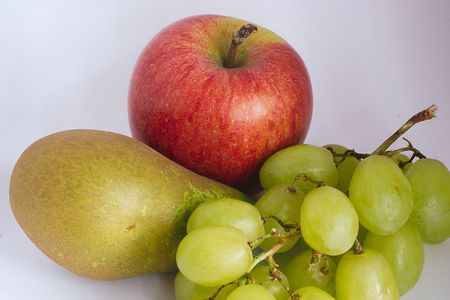 apple pear and grapes over a white background photo