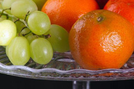 closeup shot of a satsumas and grapes on a glass plate photo
