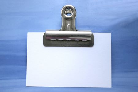note in a bullclip against a blue background Stock Photo