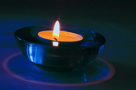 candle in a blue glass holder photo