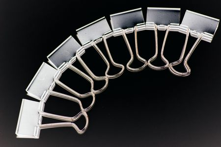 arch of binder clips over a black background Stock Photo - 327946
