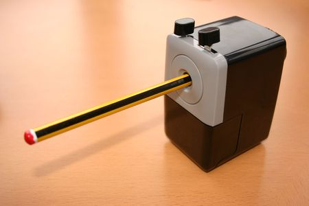 sharpen: a sharpener with a pencil in it ready to sharpen