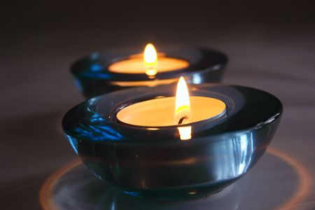 two tea candles in blue glass holders photo