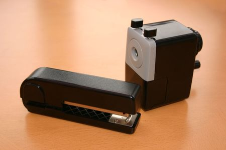 sharpener and stapler on a desk top photo