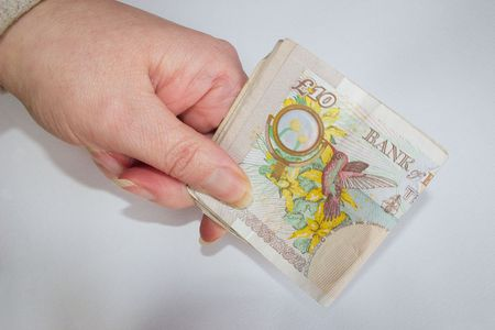 accountancy: holding folded ten pound notes Stock Photo