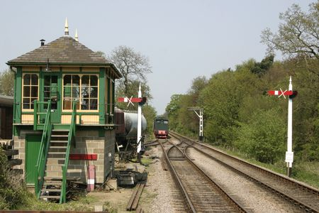 looking down the train tracks past a signal box