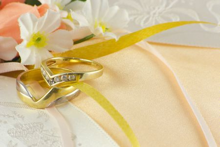wedding rings on a cushion with flowers and ribbons