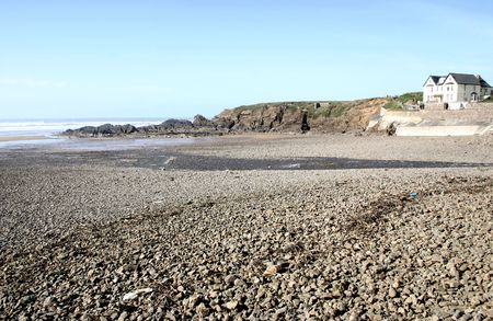 stoney: view across a stoney beach to overlooking residential buildings Stock Photo