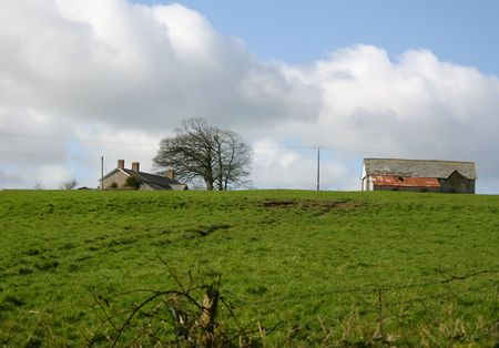 farmhouse and out-buildings on the top of a hill photo