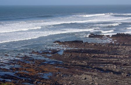 waves coming over the rocks of a rocky coastline photo