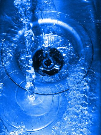blue cast water going down a plughole or drain photo