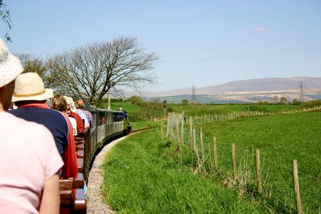 narrow gauge passenger train filled with tourists travelling through the countryside Stock Photo - 1018602