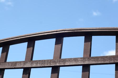 fenceline: wooden trellis set against a blue sky