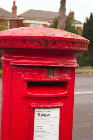 english red mailbox situated at the side of the road for public mail Stock Photo - 1944645