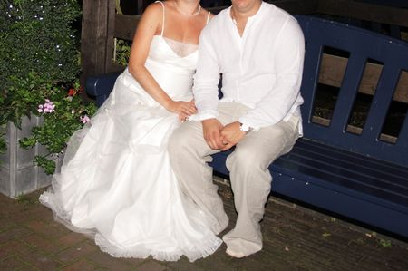 blessings: bride and groom sitting relaxed on a wooden bench