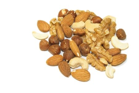 pile of mixed shelled nuts isolated over a white background