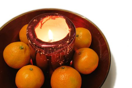 oranges set around a  candle in a red glass bowl as a table decoration against a white background Stock Photo - 2419470