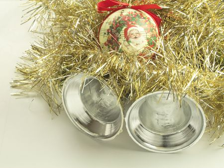 silver bells: gold and silver tinsel with a santa bauble and silver bells christmas tree decorations over a light background Stock Photo