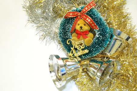 teddy wreath: gold and silver tinsel with teddy wreath and silver bells christmas tree decorations over a light background