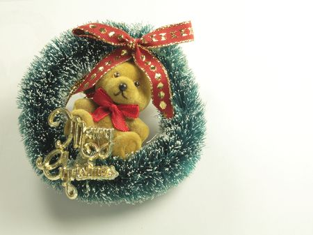 teddy wreath: teddy wreath with merry  christmas sign on it a tree decoration over a light background