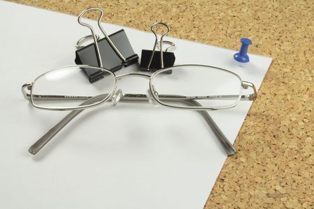 chrome spectacles and clips on a piece of paper pinned to a notice-board Stock Photo - 2583457