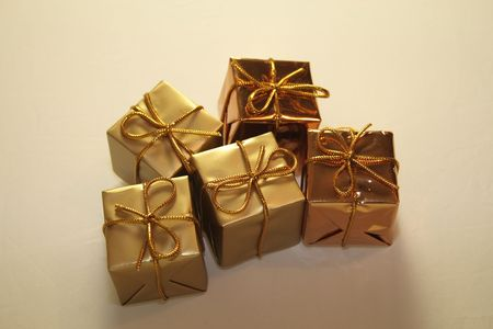fastened: gold coloured  square boxed presents fastened with bows for hanging on the  tree Stock Photo