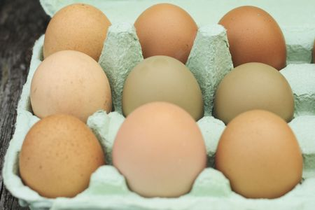 ova: fresh free-range chicken eggs of assorted sizes and colour in a green egg box Stock Photo