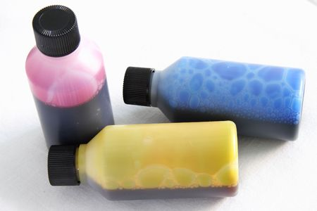 three plastic bottles with different coloured ink in each photo