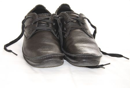 a pair of worn dark leather shoes with laces photo