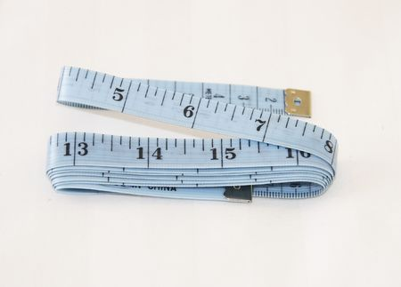 centimetres: blue tape-measure showing inches and centimetres over a light background Stock Photo