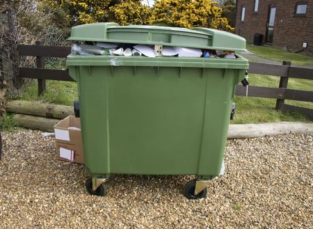 green recycle bin full of empty botles and tins