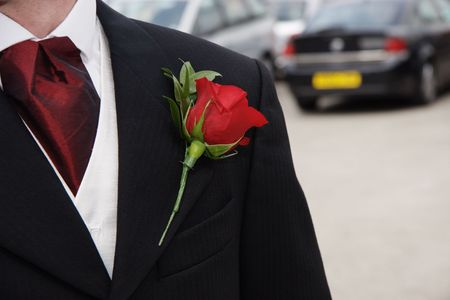 red rose pinned as a button hole on the lapel of a grooms Jacket photo