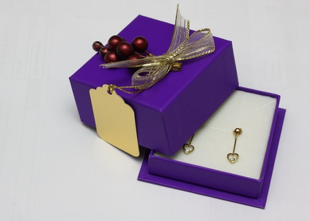 boxed: a gift of a pair of gold and diamond heart shaped earrings in a decorative purple box.