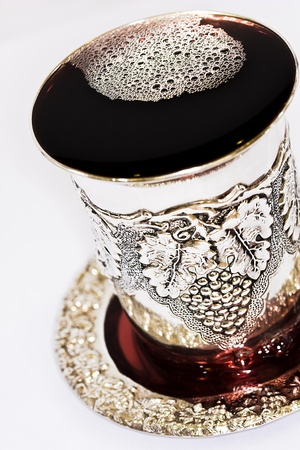 kiddush: Silver kiddush cup with bubbly red wine