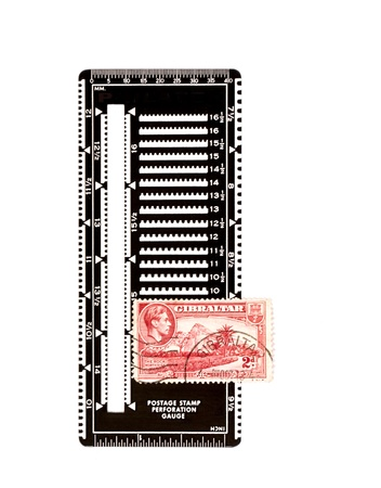 philately: Red postage stamp of Gibraltar lays on a black perforation gauge used to measure the number of holes within a 2 cm length  Used by stamp collectors to distinguish different stamps and to assess the condition of the stamp