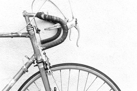 racing bike: Front of an old 10 speed racing bike with drop down handlebars laying against a wall; black and white photo