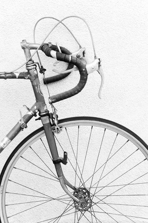 racing bicycle: Front of an old 10 speed racing bike with drop down handlebars laying against a wall; black and white photo