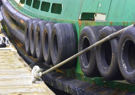 tug boat: Green and black tugboat firmly tied to a wooden dock Stock Photo