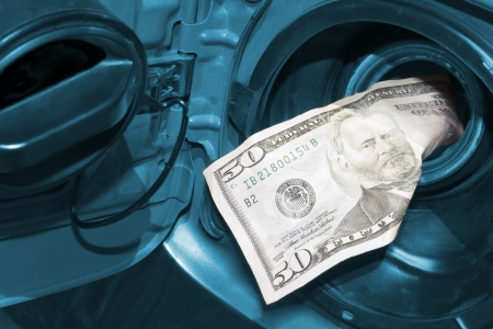 fifty dollar bill: High cost of gas is represented by a fifty dollar bill going into the gas tank Stock Photo
