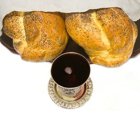 kiddush: Two partly covered challah bread loaves are shown with silver kiddush cup filled with red wine; top view, isolated on white