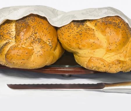 shabat: Dos barras de pan parcialmente cubiertas jal� se muestran con un cuchillo de pan reluciente descansando en el frente; aislado en blanco