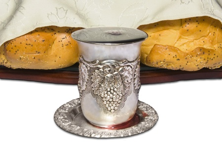 kiddush: Two partly covered challah bread loaves are shown with silver kiddush cup filled with red wine; front view, isolated on white