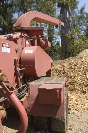 bark mulch: A wood chipper machine sits near a pile of wood chips; side, rear view