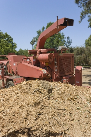 bark mulch: A wood chipper sits beside a pile of wood chips Stock Photo