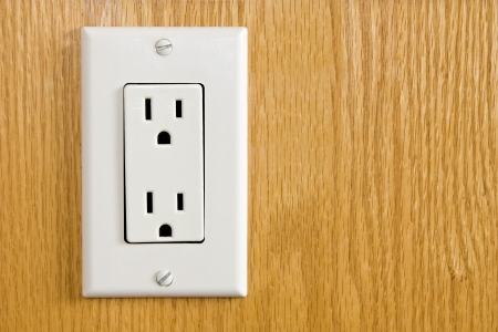 Electrical outlet with dual 3 pin plugs screwed onto wood paneling photo