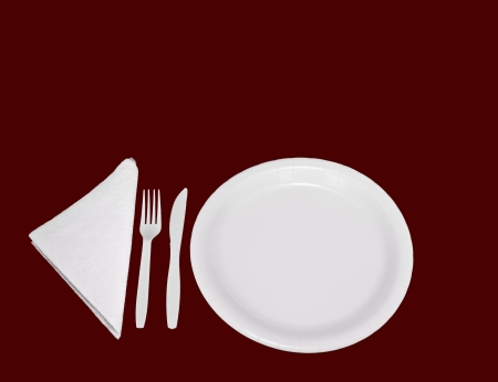 White paper plate, plastic fork and knife isolated on a red background Stock Photo - 14258830