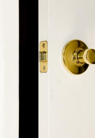 door knob: White door ajar with brass hardware and doorknob