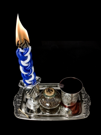 Lighted candle, spices, and kiddush cup with wine on a shiny silver tray  Havdala candle has multiple wicks and is lit after the conclusion of the Jewish sabbath; wine is served and a sweet spice is smelled  photo