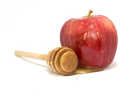 Symbol of the Jewish New Year - sweet honey flowing over a delicious apple Stock Photo - 14382813